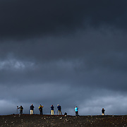 Photographers on a ridgeline photographing the changing light in Landmannalaugar, Iceland.