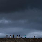 Photographers on a ridgeline photographing the changing light in Landmannalaugar, Iceland.