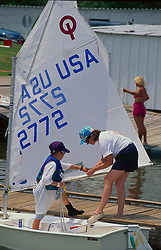 Stock photo of a woman helping a boy off of a docked sailboat