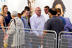 © Licensed to London News Pictures .  08/09/2012 . Manchester, UK . Domenyk Noonan (in white shirt and glasses in centre) , recently released from prison , walks along Manchester 's Market Street , accompanied by his Nephew , Kieran Noonan (in grey tracksuit) . The area was the scene of looting and rioting on 9th August 2011 , during which Noonan was arrested . Noonan has announced he plans to sue the police over the  arrest . Under the terms of a previous early release , the arrest lead to him being recalled to prison . Photo credit : Joel Goodman/LNP