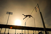 silhouette of pole vaulter going over the bar at track meet
