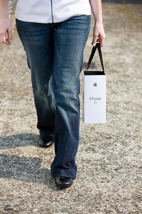 A shopper returns from purchasing an Apple 3G iPhone with product and bag in hand
