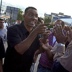A supporter of Venezuelen President Hugo Chavez argues  with a Caracas Police officer, Dec 16, 2002, outside  the Brigada Motorizada. Federal troops unsuccessfully attempted to commandeer the Police station in a tense standoff that pitted opponents and supporters of Chavez as well as National Guard and local police officers against each other.