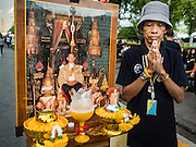 20 OCTOBER 2016 - BANGKOK, THAILAND:  A man in mourning for the late Bhumibol Adulyadej, the King of Thailand, stands his next to his home made shrine and prays for the King on Sanam Luang. Sanam Luang, the Royal Ceremonial Ground, is packed with people mourning the Monarch's death. The King died Oct. 13, 2016. He was 88. His death came after a period of failing health. Bhumibol Adulyadej was born in Cambridge, MA, on 5 December 1927. He was the ninth monarch of Thailand from the Chakri Dynasty and is also known as Rama IX. He became King on June 9, 1946 and served as King of Thailand for 70 years, 126 days. He was, at the time of his death, the world's longest-serving head of state and the longest-reigning monarch in Thai history.       PHOTO BY JACK KURTZ