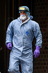 © Licensed to London News Pictures. 19/05/2016. London, UK. A member of a Police forensics team leaves a property  at the Maitland Park Estate in Hampstead, North London, where the body of a woman in her 40s was found.   A murder investigation has been launched. Photo credit: Ben Cawthra/LNP