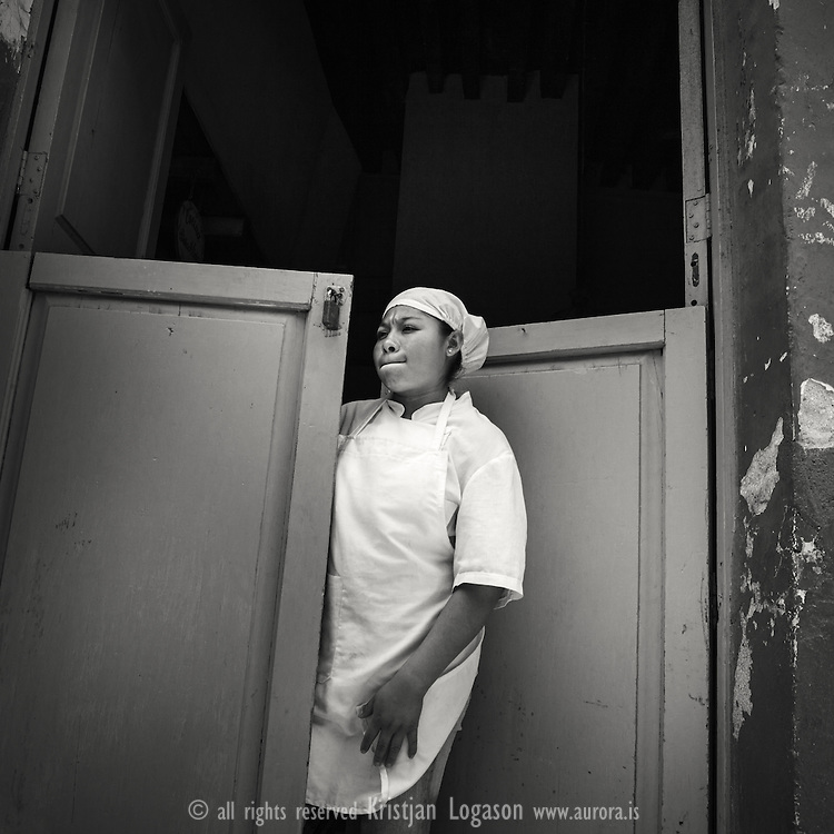 Woman worker in a restaurant taking a brake looking out of the kitchen door