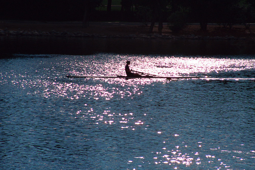 A rower moves across the sun dappled waters of Wascana Lake, Regina Saskatchewan