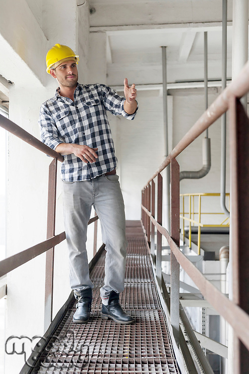 Full length of young male worker gesturing on metal aisle in industry