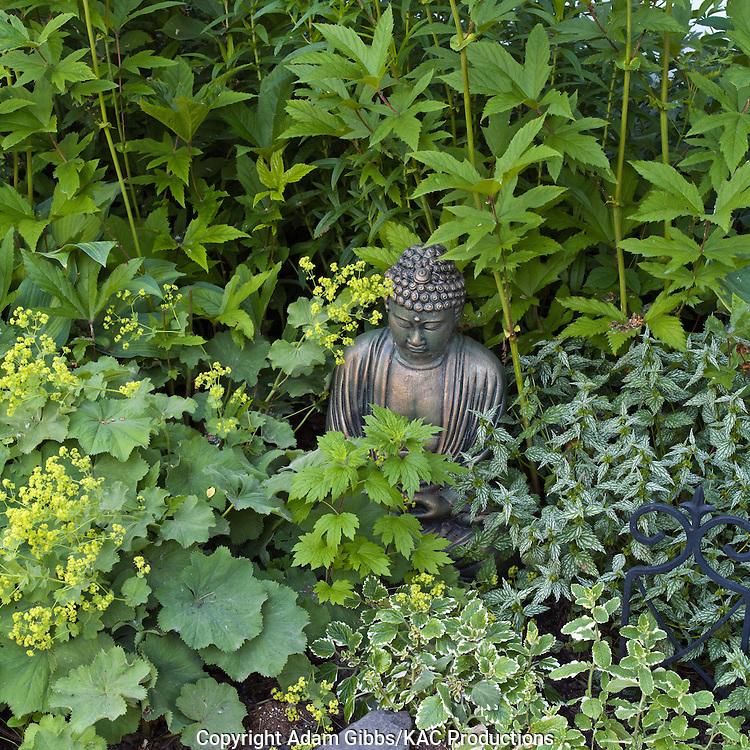 garden ornament amongst alchmilla mollis and other perennials