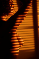 Artistic nude photo of a topless woman standing in light coming through window blinds leaving a stripy pattern on the outline of her breast