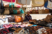 TETOUAN, MOROCCO - 5th April 2016 - Portrait of a hand bag and clothing items seller sat at his stall in the Tetouan Medina, Rif region of Northern Morocco.