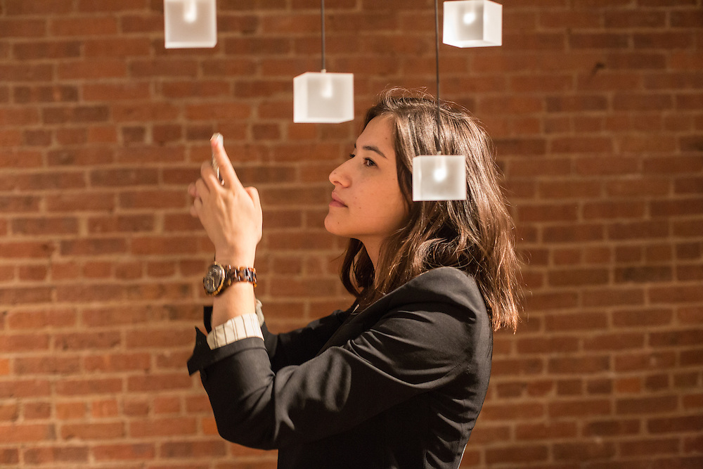 A woman takes a photo of a lighting fixture made of LED-lit cubes by Graypants, a design firm based in Seattle and Amsterdam. This is a small part of the fixture, whih includes about 200 cubes.