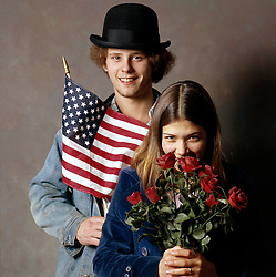 young hippie couple with american flag bowler hat and red roses
