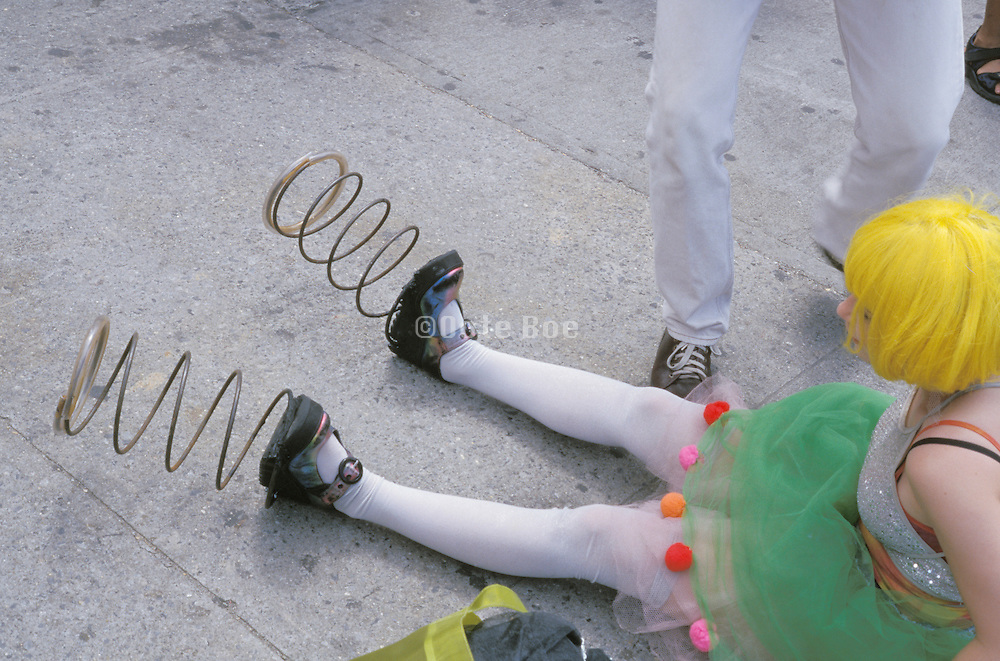 Girl in costume sitting on the ground with springs on her feet