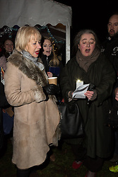 © Licensed to London News Pictures. 08/12/2014. London, UK. Helen Mirren sings Christmas carols. Dame Helen Mirren turns on the Christmas tree lights at Wapping Green in Tower Hamlets, East London tonight. This is the first time in many years that Wapping has had a Christmas tree and Dame Helen Mirren surprised residents by turning up at the community event and leading the countdown to switching the tree lights on. She then joined residents singing carols and drinking mulled wine, at the event which was arranged by the local councillor for Wapping and St Katharines, Julia Dockerill. Photo credit : Vickie Flores/LNP
