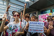 """01 JUNE 2014 - BANGKOK, THAILAND: Thais hold up a three fingered salute during a protest against the Thai military coup at Terminal 21 a popular shopping mall in Bangkok. The salute is from the movie """"The Hunger Games"""" and symbolizes it admiration, thanks and good-bye to a loved one. In this case, the loved one is reportedly Thai democracy. The Thai army seized power in a coup that unseated a democratically elected government on May 22. Since then there have been sporadic protests against the coup. The protests Sunday were the largest in several days and seemed to be spontaneous """"flash mobs"""" that appeared at shopping centers in Bangkok and then broke up when soldiers arrived. Protest against the coup is illegal and the junta has threatened to arrest anyone who protests the coup. There was a massive security operation in Bangkok Sunday that shut down several shopping areas to prevent the protests but protestors went to malls that had no military presence.    PHOTO BY JACK KURTZ"""