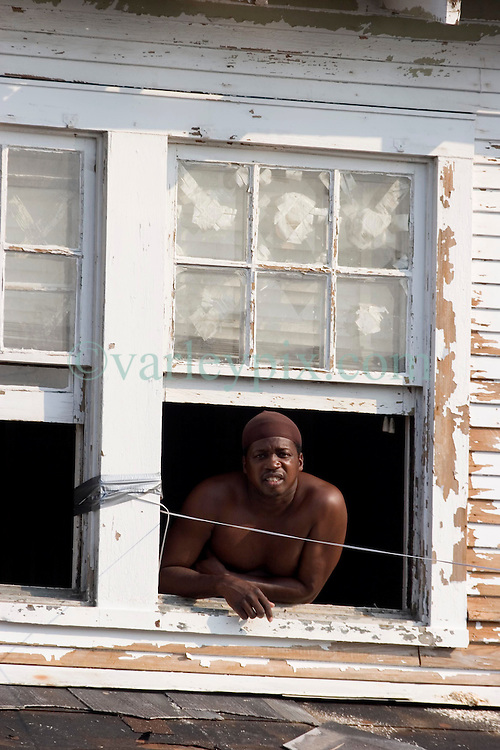 05 Sept  2005. New Orleans, Louisiana. Post hurricane Katrina.<br /> Residents who refuse to leave. Leaning from a top floor window above the water level, Rogers Jefferson, a resident of Uptown New Orleans refuses to leave the devastated flood areas.<br /> Photo; ©Charlie Varley/varleypix.com