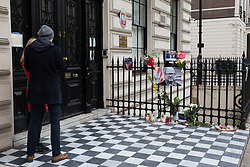 London, UK. 19th January, 2019. Two people pay their respects in front of tributes to Paweł Adamowicz outside the Polish embassy, the Mayor of Gdansk who died on Monday after having been fatally stabbed the previous evening at a charity event. Thousands of Poles attended his funeral in Gdansk today. Mr Adamowicz served as the mayor of his home city of Gdansk for 20 years and was well-known for his liberal views and as a critic of the anti-immigration policies of Poland's ruling party.