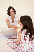 Mother using lap top handing daughter teddy bear sitting on bed