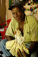 A craftsman with his doll in Barranco, a traditional Garifuna village in southern Belize.  The doll carries sticks of firewood on her head.