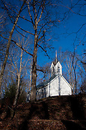 Historic white church stands out against the trees and blue sky in the backwoods of the Great Smoky Mountains National Park