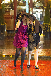 """© Licensed to London News Pictures . 15/12/2012 . Manchester , UK . Two women shelter from the rain beneath an overcoat . Revellers enjoy a wet but busy night out on one of the last weekends before Christmas , a traditionally busy time when office parties and clubbers decent on bars and clubs , often known as """" Mad Friday """" . Photo credit : Joel Goodman/LNP"""